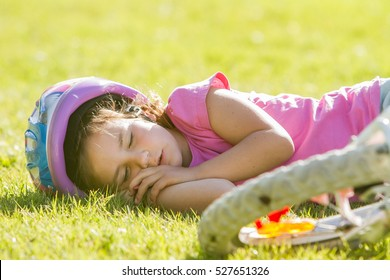 young caucasian child girl sleeping near her bike on natural background