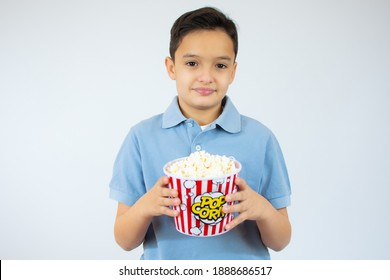 Young caucasian child with popcorn on white background