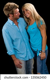 Young Caucasian Couple in blue shirts and jeans embracing. Shot on a black background.