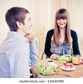 Young caucasian couple dining in restaurant and smiling.