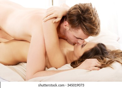 Young caucasian couple kissing on bed.