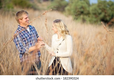 Young Caucasian couple playing in tall grass