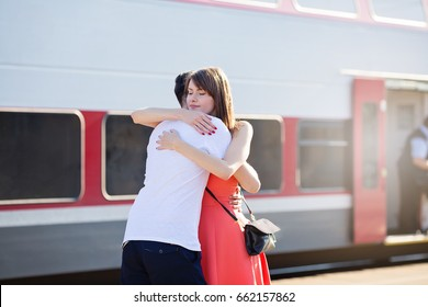 Young caucasian couple standing at the train station, hugging for goodbye