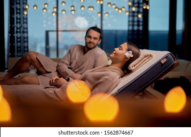Young caucasian couple take rest in spa salon lying in bathrobes together and relax with candles