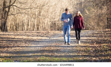 Young caucasian couple walking on dim gravel, dirt, rural, country road holding hands, kissing,smiling, laughing in love having fun season late winter bare trees