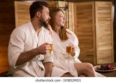 young caucasian couple in white bathrobe sit relaxing, enjoying tea in spa salon