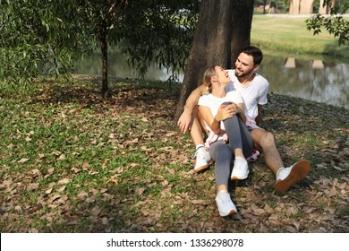 young caucasian couple who wearing white shirt are in love, sitting and embracing in park during summer season with trees (friendship or valentine concept)