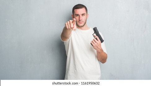 Young caucasian criminal man over grey grunge wall holding gun pointing with finger to the camera and to you, hand sign, positive and confident gesture from the front
