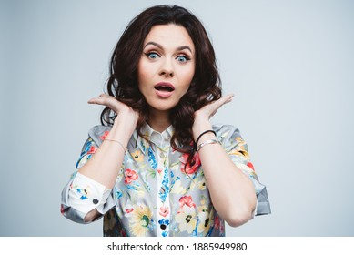 Young caucasian curly hair brunette 40 years old woman with blue eyes and nude make-up in the color shirt in the studio. Emotional shot with surprise emotion.