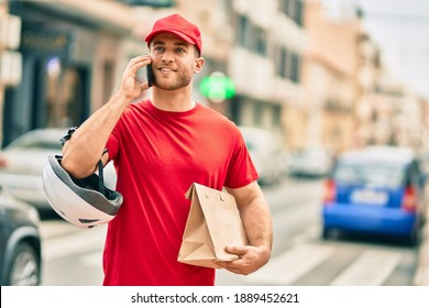 Young caucasian deliveryman talking on the smartphone and holding delivery paper bag at the city.