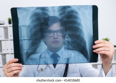 Young caucasian doctor holding chest x-ray on bookshelf background