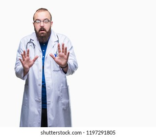 Young caucasian doctor man wearing medical white coat over isolated background afraid and terrified with fear expression stop gesture with hands, shouting in shock. Panic concept.
