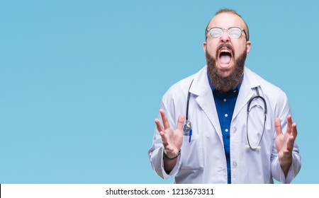 Young caucasian doctor man wearing medical white coat over isolated background crazy and mad shouting and yelling with aggressive expression and arms raised. Frustration concept.