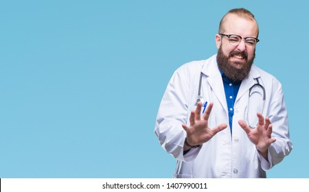 Young caucasian doctor man wearing medical white coat over isolated background disgusted expression, displeased and fearful doing disgust face because aversion reaction. With hands raised. Annoying