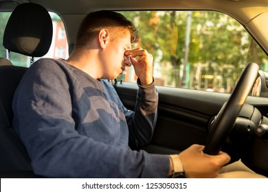 Young Caucasian driver falling asleep sitting inside her car, rubbing eyes, stopped to rest. Tired man having headache after driving. Exhausted, sleepiness, overworked driver concept.