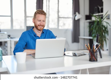 Young Caucasian employee sitting in office and typing on laptop. Start up business concept.