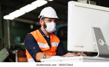 Young caucasian engineering man worker working on digital tablet computer at manufacturing. Worker man wearing face mask prevent covid-19 virus and protective hard hat.