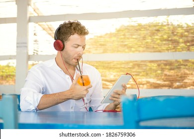 Young caucasian european guy dinking cocktail working with tablet as freelance in outdoor smart working concept