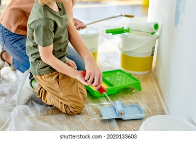 young caucasian family renovating painting wall house. Mother and child son repairing paint wall at home. Together love family lifestyle concept with copy space. close-up using roller and paints