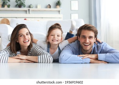Young Caucasian family with small daughter pose relax on floor in living room, smiling little girl kid hug embrace parents, show love and gratitude, rest at home together