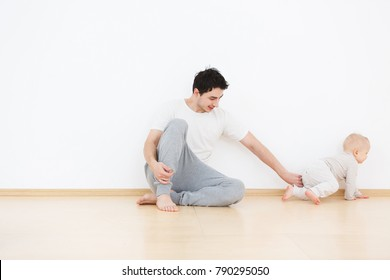 Young caucasian father having fun with his little son one years old. Sitting on wodden floor in cozy interior on white wall background. Happy fatherhood