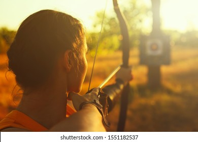 Young Caucasian female archer shooting with a bow in a field at sunset.