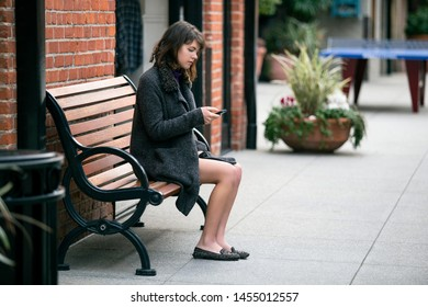 Young Caucasian female commuter at a bus stop or train station or a rideshare.  She is sitting on a bench and waiting patiently.  She is browsing on her cell phone.