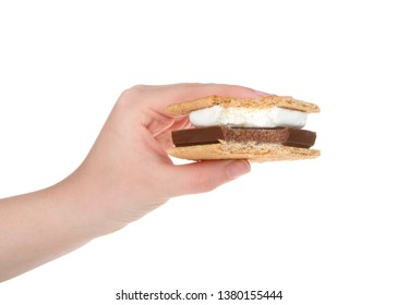 Young caucasian female hand holding s'more with bite missing, isolated on white background