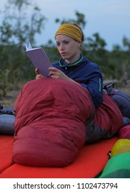 young caucasian female reading book while outdoor camping