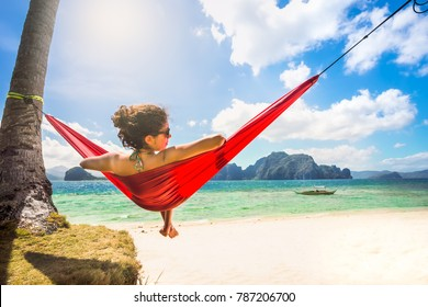 Young caucasian female relaxing in a red hammock on a tropical beach
