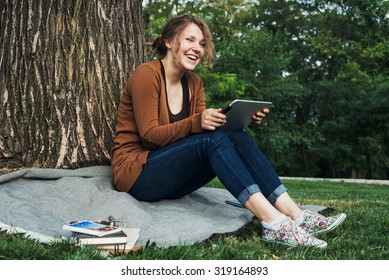 young caucasian female student with tablet on campus, student study in campus area using tablet