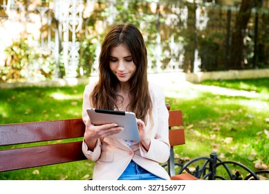 young caucasian female student with tablet on campus