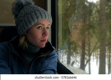 young caucasian female traveling on train, looking from window on a winter landscape