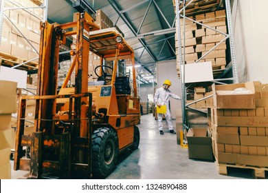 Young Caucasian female worker in uniform and protective helmet holding folder and counting boxes. In foreground forklift.