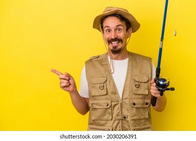 Junge, kaukasische Fischer, die eine Stange einzeln auf gelbem Hintergrund halten, lächeln und zeigen beiseite, zeigen etwas an Leerraum.