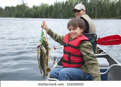 A young caucasian fisherman proudly holds up a stringer of walleyes