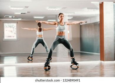 Young Caucasian fit sporty woman in sportswear doing fitness exercises with kangoo jumps footwear. In background mirror.