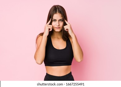 Young caucasian fitness woman doing sport isolated focused on a task, keeping forefingers pointing head.
