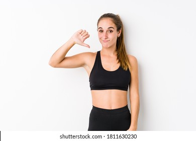 Young caucasian fitness woman posing in a white background showing a dislike gesture, thumbs down. Disagreement concept.