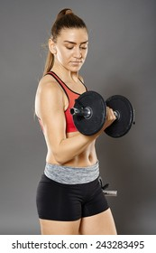 Young caucasian fitness woman working with dumbbells, studio shot