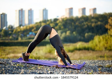 young caucasian flexible woman do yoga exercises on mat, with head bowed, concentrated on exercise, fit female begin morning with yoga in in city while poeple are still sleeping