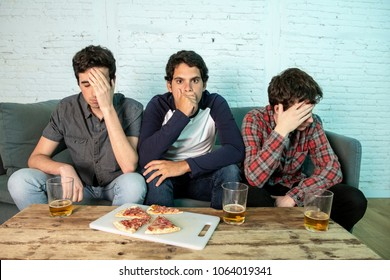 young caucasian football fans disappointed and angry watching a football game on the couch.