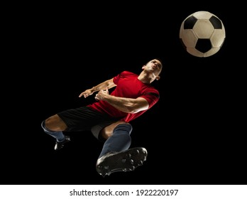 Young caucasian football, soccer player in action, motion isolated on black background, look from the bottom. Concept of sport, movement, energy and dynamic, healthy lifestyle. Training, practicing.