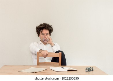 Young Caucasian freelancer man sitting in his home office at the table, drinking water in front of empty clear wall.