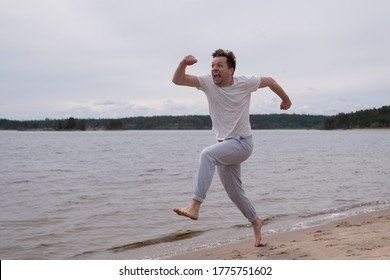 Young caucasian funny man in fitness clothing running along sandy beach