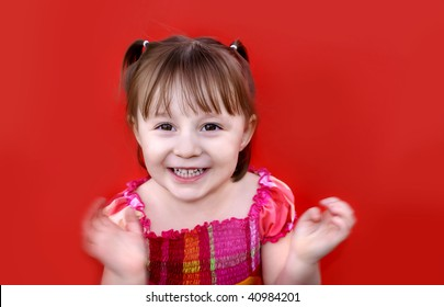 Young caucasian girl (2 years old) in pigtails wearing a red and pink plaid dress smiles and claps her hands in excitement. Shot against a red backdrop.