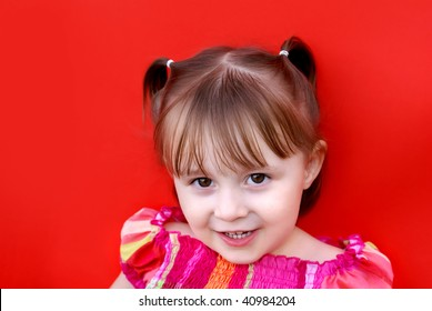 Young caucasian girl (2 years old) in pigtails wearing a red and pink plaid dress smiles and looks up. Shot against a red backdrop.
