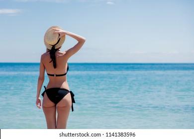 Young caucasian girl in black bikini on a beach in summertime. Odessa, Ukraine