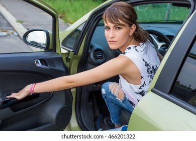 Young caucasian girl in car with the door opened looking back. Angry. Car broken.