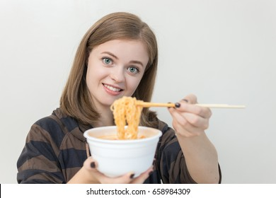 Young caucasian girl eating noodles using chopsticks